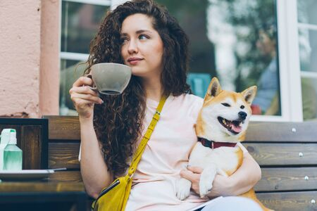 Attractive girl is drinking tea outdoors in cafe and patting cute shiba inu dog sitting on bench in the street enjoying day out. People, pets and lifestyle concept.