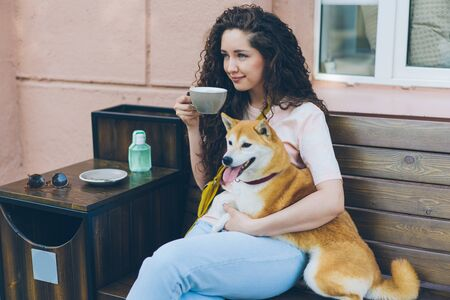 Young lady is drinking tea and hugging shiba inu dog outdoors in cafe sitting on bench smiling enjoying leisure time. People and domestic pets concept.
