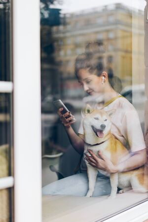 Pretty woman in wireless earphones is using smartphone and hugging dog in cafe sitting on comfortable window sill. People, relaxation and hobby concept.
