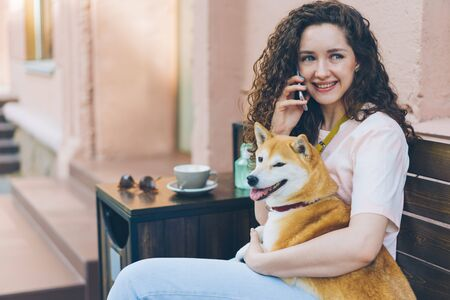 Beautiful young lady pet owner is speaking on mobile phone and hugging shiba inu dog outdoors in cafe sitting on bench in the street. People and devices concept.