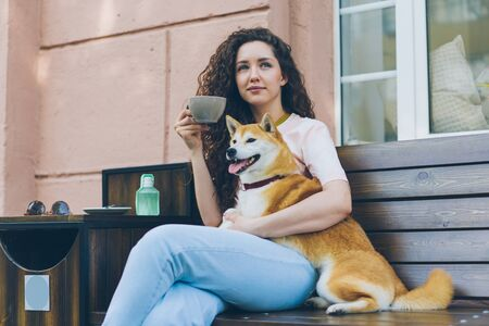 Beautiful woman is relaxing outdoors in cafe with pet dog and cup of coffee sitting on wooden bench smiling enjoying leisure time. People and relaxation concept. Stock fotó