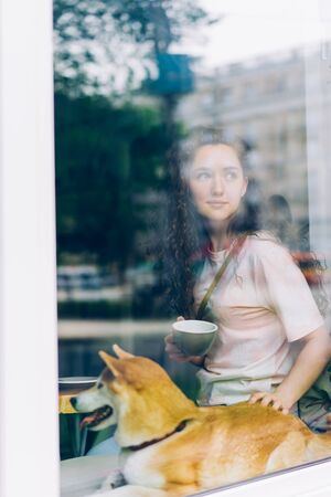 Pretty young woman is drinking coffee and stroking cute puppy sitting on window sill in cafe looking outside. People, relaxation and pets concept. Imagens
