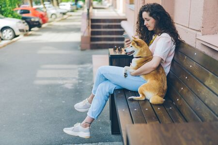 Smiling girl is using smartphone touching screen and hugging adorable shiba inu dog outdoors in the street cafe sitting on bench. People, devices and pets concept.