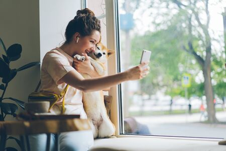 Cheerful lady taking selfie with doggy in cafe using smartphone camera sitting on window sill having fun with cute animal. People and technology concept.