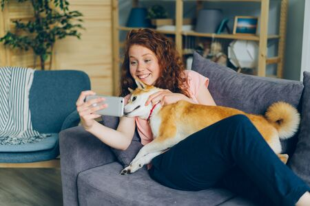 Young dog owner attractive girl is taking selfie with cute pet shiba inu puppy smiling using smartphone camera at home. Modern technology and photography concept.