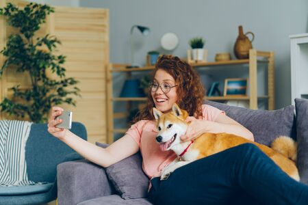 Happy young girl is taking silfie with lovable dog using smartphone camera having fun sitting on couch holding device. Youth and domestic animals concept. Imagens
