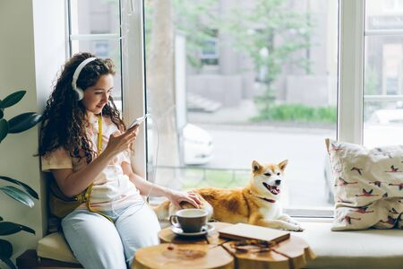 Pretty girl is listening to music with headphones and using smartphone sitting on window sill in cafe with lovely well-bred dog lying near her. Youth and pets concept.