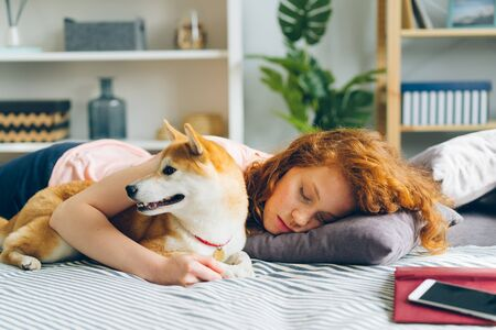 Beautiful young lady is sleeping on couch at home hugging adorable puppy lying together resting. Youth lifestyle, happy people and animals concept.