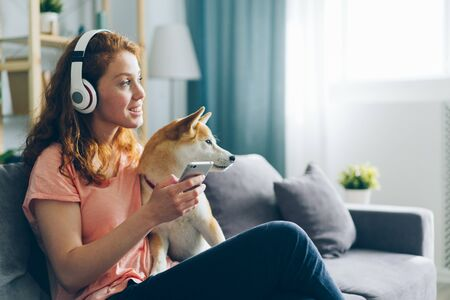 Beautiful woman in headphones is listening to music and petting pedigree dog sitting on couch enjoying song holding smartphone. Happiness, animals and youth culture concept. Imagens