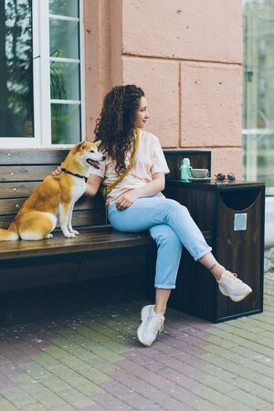 Beautiful curly-haired girl is sitting in street cafe with cute purebred dog smiling looking around enjoying warm summer day. People and pets concept.