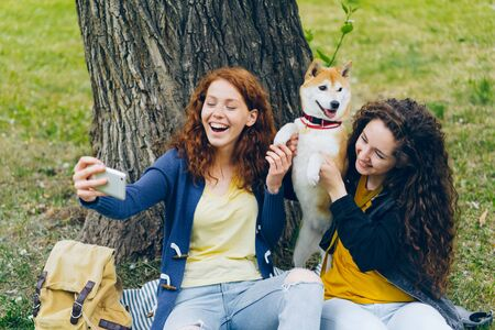 Loving dog owners attractive curly-haired girls are taking selfie with pet in park using smartphone camera holding animals paws. People and emotions concept.