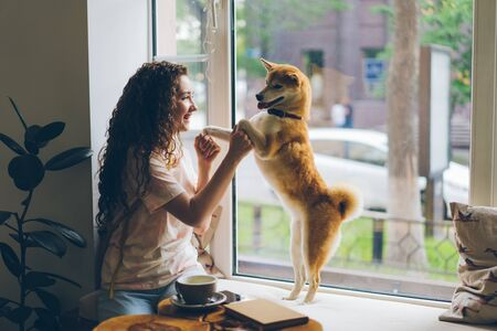 Happy young woman is dancing with pet dog sitting on window sill in cafe having fun enjoying music and animal. Modern lifestyle, people and youth concept. Stock Photo