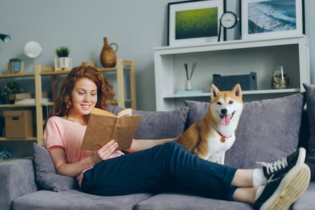 Attractive girl student is reading book and stroking lovable shiba inu puppy sitting on couch in flat enjoying literature. Hobby, youth and leisure activity concept.