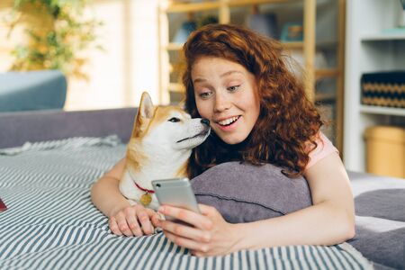 Happy young woman is taking silfie with adorable dog using smartphone camera having fun lying on couch holding device. Youth and domestic animals concept.