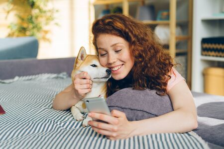 Pretty girl is taking silfie with lovable puppy using smartphone camera having fun lying on sofa holding device. Youth and domestic animals concept. Imagens