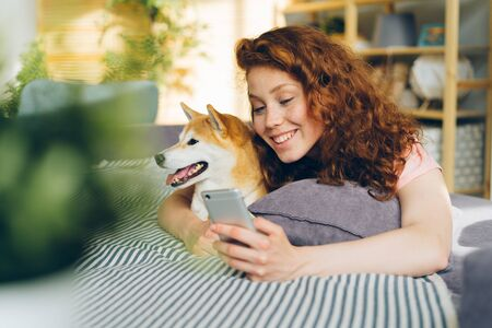 Joyful girl taking picture with shiba inu dog using smartphone to take selfie lying on couch at home holding device and posing. People and photograph concept.