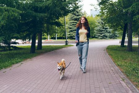 Pretty woman with smartphone walking shiba inu dog in park on summer day smiling enjoying summertime and relaxing walk. Youth, lifestyle and leisure time concept.