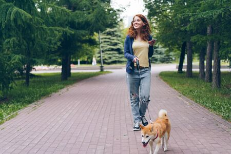 Cute girl student is walking with shiba inu dog in green park holding smart phone smiling enjoying summer day. People, gadgets and modern lifestyle concept. Imagens