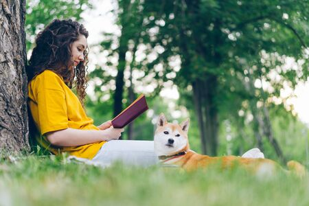 Side view of beautiful young woman reading book in park with shiba inu puppy on summer day relaxing outdoors with beloved pet. People and animals concept. Imagens