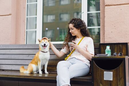 Smiling young lady is stroking beautiful shiba inu dog and holding cup of coffee in street cafe sitting on wooden bench enjoying day out. Youth and pets concept. Imagens