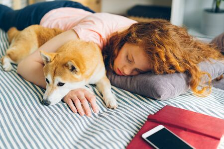 Attractive young woman and cute shiba inu dog are sleeping together at home on bed hugging enjoying relaxation. Humans and animals friendship concept.