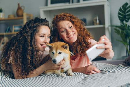 Pretty girls friends are taking selfie with cute dog using smartphone camera lying on couch together having fun. Modern technology, people and photographs concept.