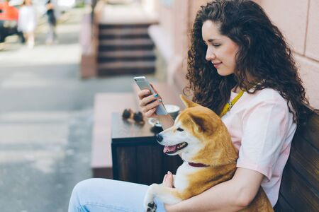 Young woman is using smartphone enjoying social media with dog in street cafe sitting on wooden bench holding device hugging animal. People and pets concept. Imagens