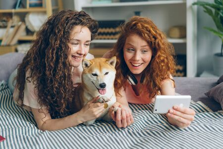 Joyful sisters attractive girls are taking selfie with adorable doggy using smartphone camera lying on couch at home smiling having fun. People and self portrait concept. Imagens