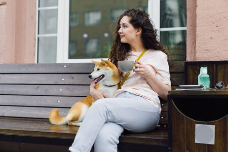 Pretty girl sitting in street cafe with cup of tea and shiba inu dog smiling enjoying free time and relaxing on summer day. People, animals and drinks concept.