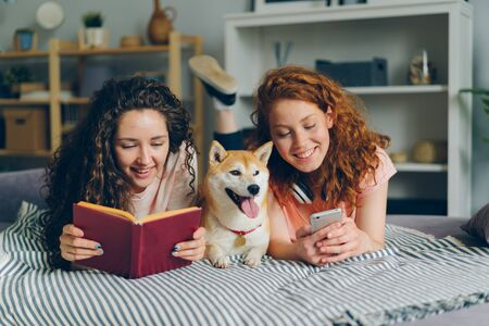 Girls friends are reading book and using smartphone lying on bed with cute shiba inu dog in cozy apartment. Modern lifestyle, friendship and animals concept. Imagens
