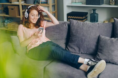 Smiling girl is listening to music through headphones and using smartphone relaxing on sofa at home having fun. Gadgets, happy youth and leisure concept. Imagens