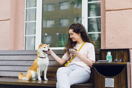 Happy young woman is drinking tea outdoors in cafe and stroking cute shiba inu puppy enjoying drink, summer and friendship with animal. People and dogs concept.