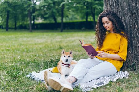 Pretty curly-haired girl young student is reading book sitting in park on lawn while her well-bred dog is lying near her on blanket. People and lifestyle concept. Imagens