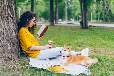 Relaxed girl is holding coffee and reading book in park sitting on lawn with shiba inu dog enjoying leisure time. Modern lifestyle, people and pets concept. Imagens