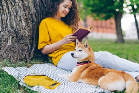 Attractive student girl is reading book in park sitting on lawn with shiba inu dog on warm summer day enjoying literature and fresh air. People and lifestyle concept.