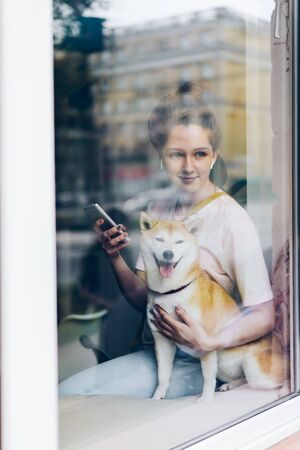 Portrait of beautiful girl sitting on window sill in cafe with dog, smartphone and earphones listening to music and looking outside in the street. Imagens