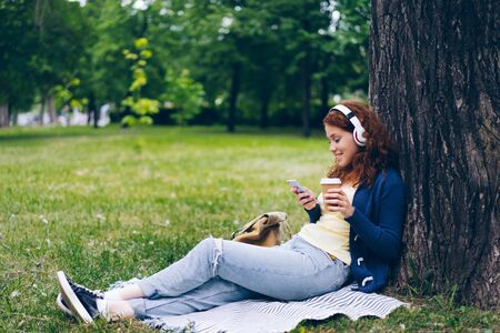 Lady in wireless headphones is enjoying music using smartphone and drinking take out coffee sitting on grass in park. Happy millennials and lifestyle concept.