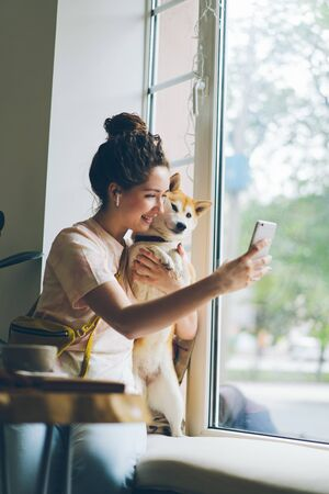 Happy lady is taking silfie with adorable dog using smartphone camera having fun sitting on window sill in cafe holding device wearing wireless earphones. Youth and animals concept.