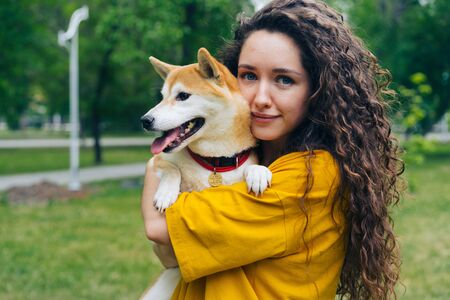 Portrait of pretty girl loving dog owner standing in park with her beautiful pet, smiling and looking at camera. Adorable animals and summer nature concept. Banco de Imagens