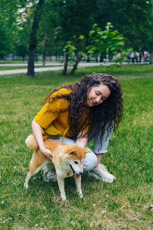 Beautiful young woman is touching shiba inu dog in park on green lawn looking at pet with love. Domestic animals, lifestyle and summer nature concept. Imagens