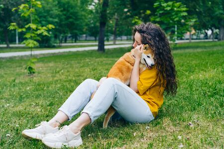 Pretty young woman is hugging shiba inu dog and smiling sitting on grass in park enjoying friendship with animal. People, affection and cute pets concept. Imagens