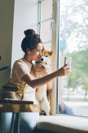 Cute woman taking selfie with shiba inu dog sitting on window sill in cafe using smartphone camera holding device posing smiling. People and animals concept. Imagens