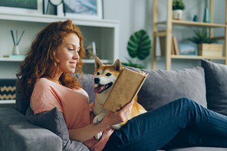 Pretty student young woman is reading book in cozy apartment smiling and petting adorable dog sitting on comfy couch at home. Animals and hobby concept.