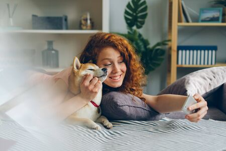 Teenage girl taking selfie with cute puppy using smartphone at home lying on couch in studio apartment smiling posing. People, animals and photographs concept. Imagens