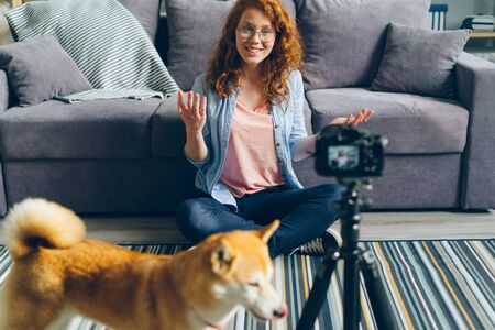 Cute teenager popular blogger is recording videoblog sitting on floor at home, stroking lovely pet dog and talking to subscribers. Social media and people concept.