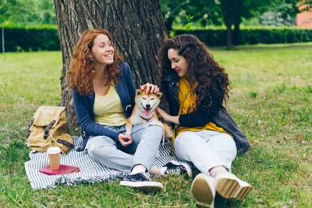 Attractive young girls friends sitting on lawn in park with cute dog talking and having fun on beautiful summer day. People, conversation and animals concept.
