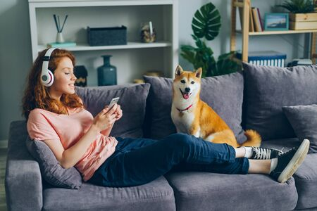 Joyful female student in headphones is listening to music and using smartphone sitting on couch with adoranle well-bred dog. People and modern lifestyle concept. Imagens