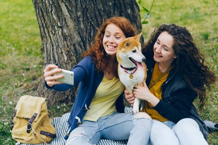 Happy girls friends are taking selfie in park with cute shiba inu dog using smartphone camera sitting on lawn having fun. Technology and youth concept.