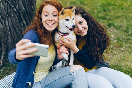 Curly-haired girls sisters taking selfie in park hugging beautiful shiba inu dog using smartphone camera posing and smiling. People, modern lifestyle and devices concept.