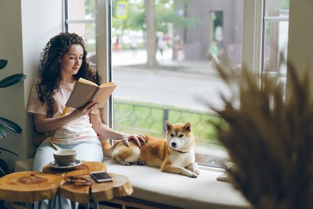 Female student is reading book and stroking pet dog sitting on window sill in cafe enjoying hobby and leisure time. Literature, animals and youth lifestyle concept. Imagens